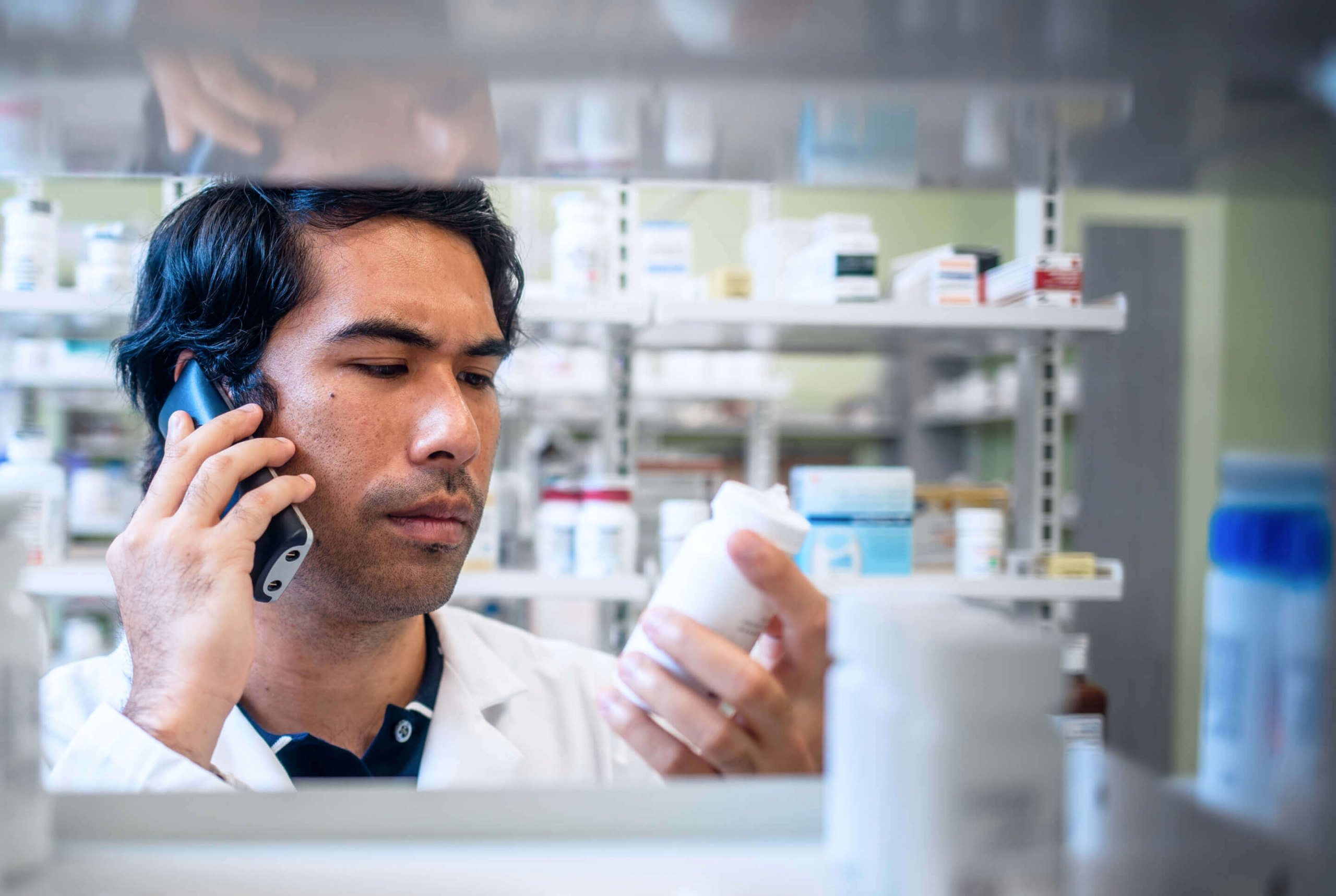 man on phone in pharmacy looking at prescription bottle