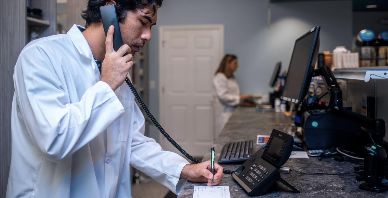 pharmacist on landline taking prescription