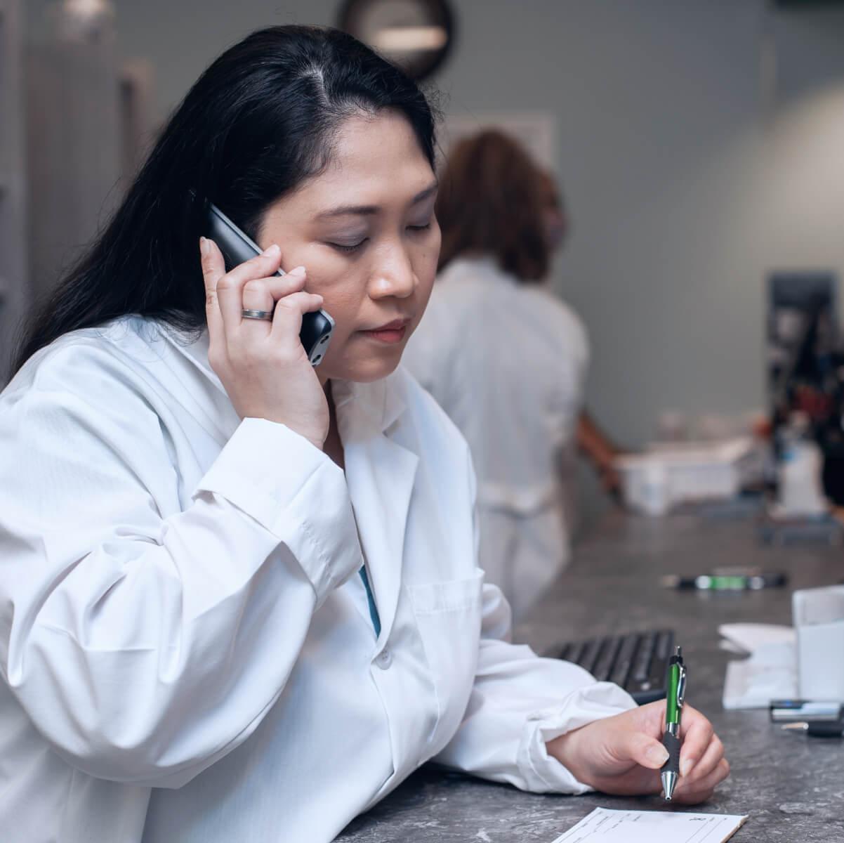 pharmacist on phone with prescription pad
